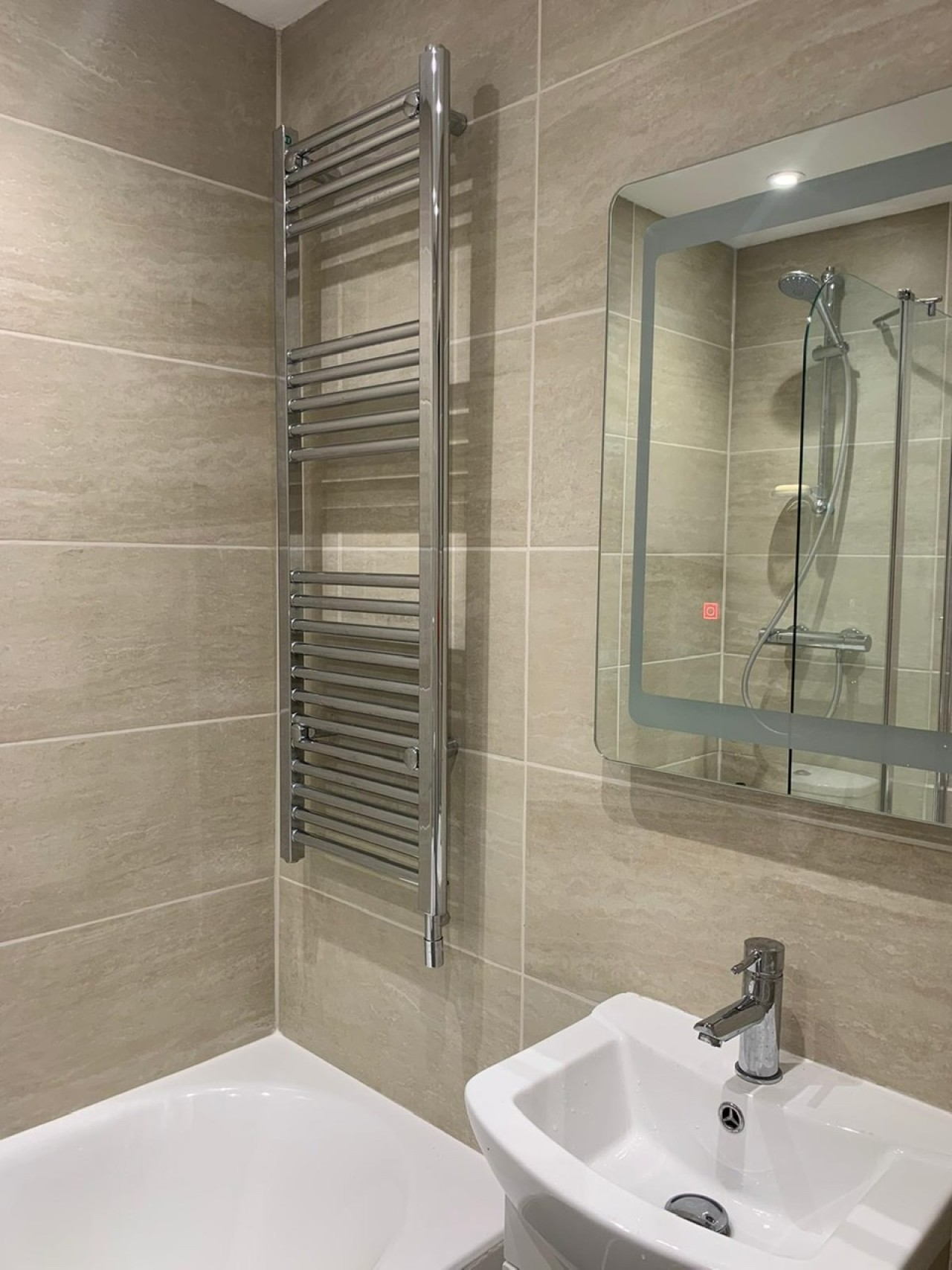 New en suite bathroom with bath and hand held shower and loo